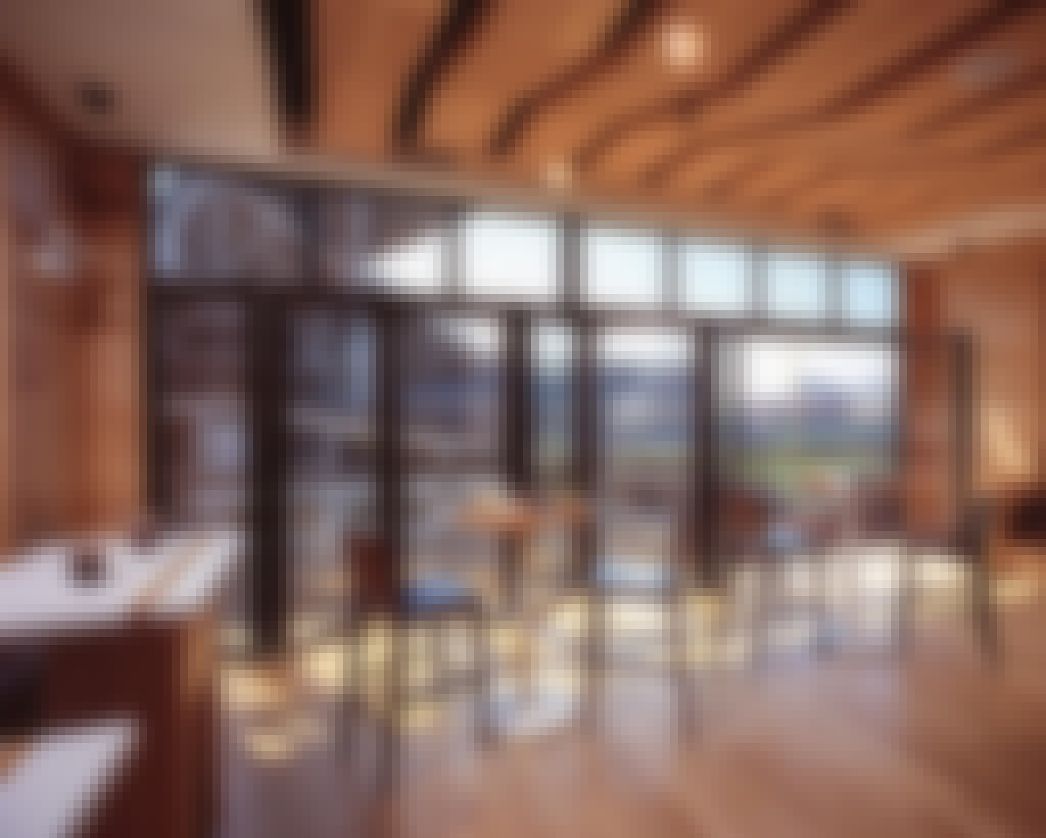 commercial folding glass wall system partially open with view of baseball view for live games