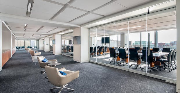 office interior with white club chairs with acoustic frameless moveable interior glass walls