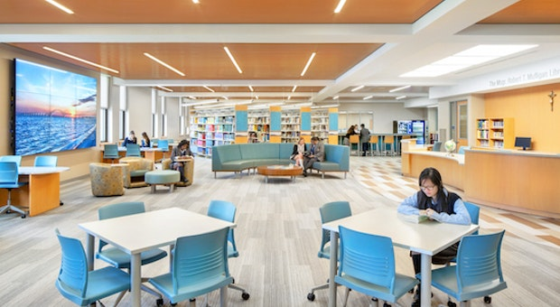 students sitting inside library room with opening glass walls