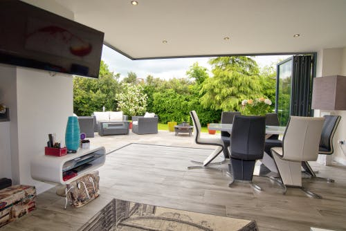 Modern-dining-area-with-tall-glass-bifold-doors-opening-to-patio