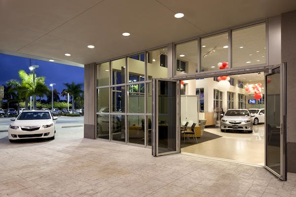 Folding glass wall large opening in auto dealership exterior