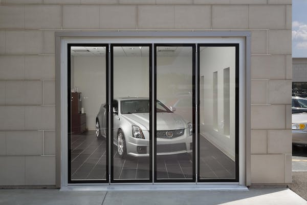 Closed commercial glass sliding door system in auto showroom exterior