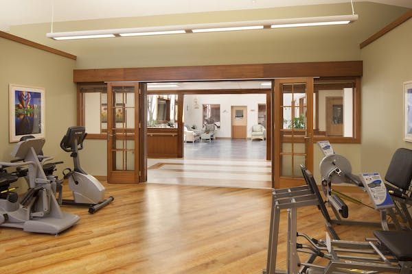 Fitness area with wood framed operable interior glass systems partitions in seniot living facility