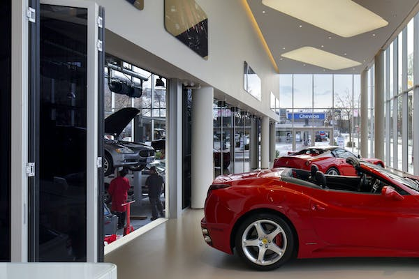 Red Ferrari inside the showroom with commercial glass wall systems separating service area