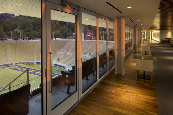 Closed Commercial Operable Glass Wall with view of the field with natural light.