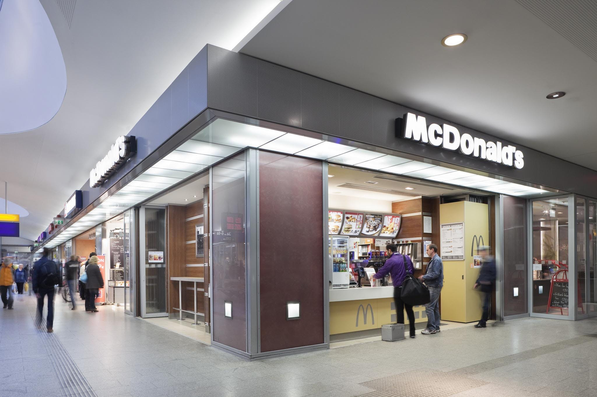 man standing near open interior commercial glass systems used as storefront for McDonalds