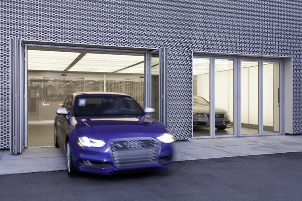 audi car being driven through commercial glass sliding door systems at dealership