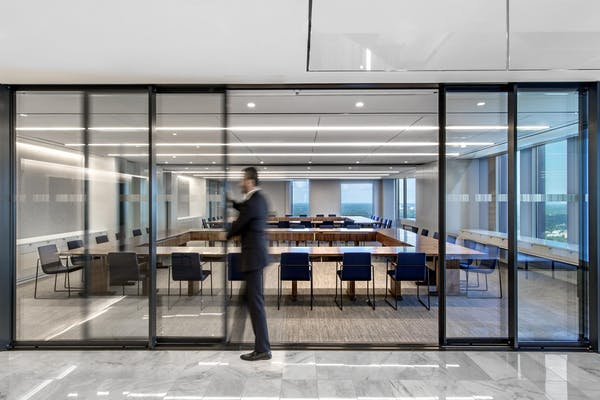 office employee opening Moveable Interior Glass Walls that offer acoustic buffering and transparency