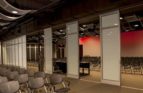 meeting space with beige chairs near aluminum sliding glass doors partition