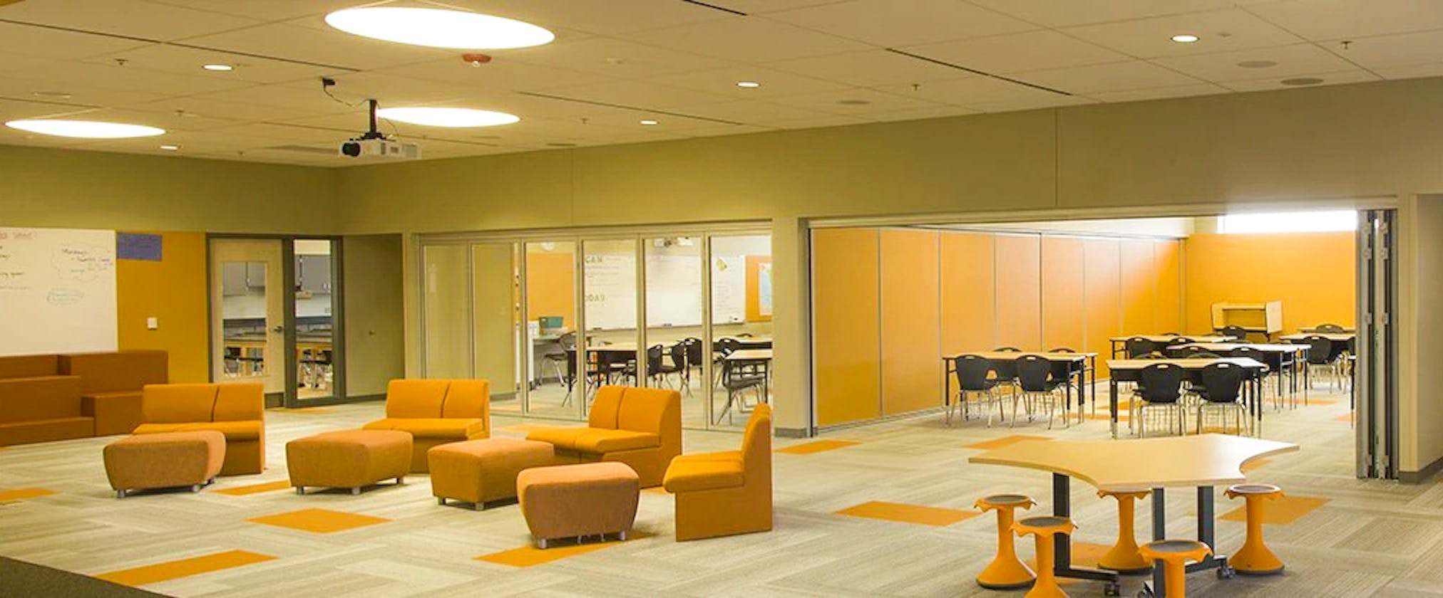 collaboration hub in elementary school with acoustic moveable glass walls in classrooms