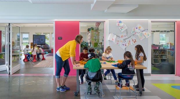 teacher standing and students in collaboration hub with folding glass walls